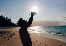 A man drinking bottled water on a sunny beach