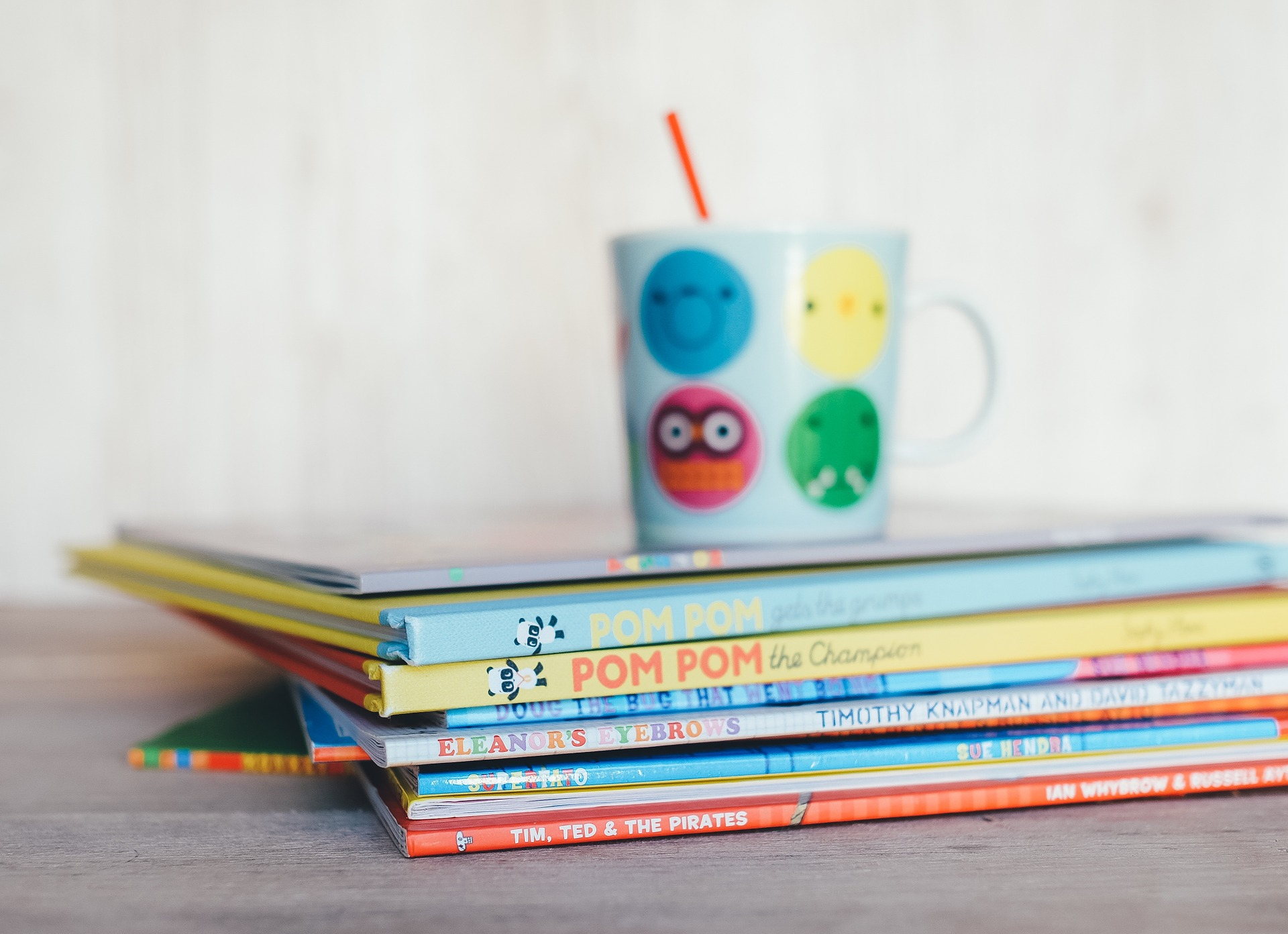 at the top of the children books is a baby cup with red straw