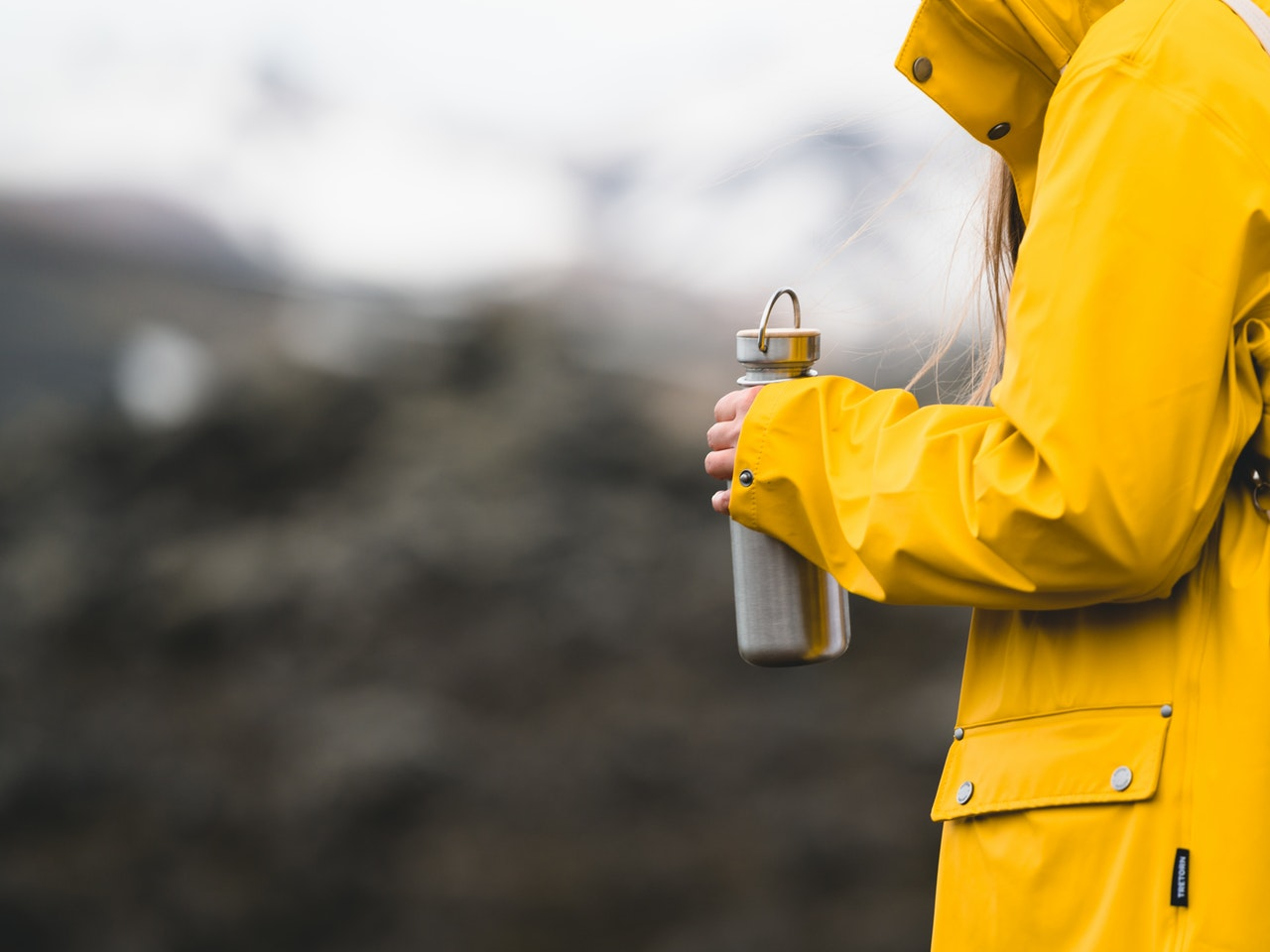 person in yellow coat holding a hydro flask vs yeti tumbler