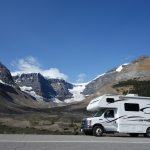 An RV with one of the best rv water softener systemson a road in fron of mountains